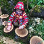 Child playing with tree rounds